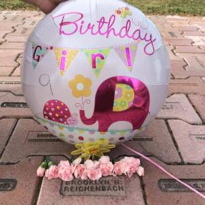 Memorial brick with birthday balloon and flowers